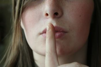 Image of a Woman Holding Her Finger to Her Lips, Representing How to Find Hidden Assets in a NJ Divorce
